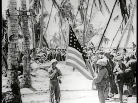 Marines gathered on beach raising American flag on rope tied to coconut tree VS Marines saluting WWII World War II