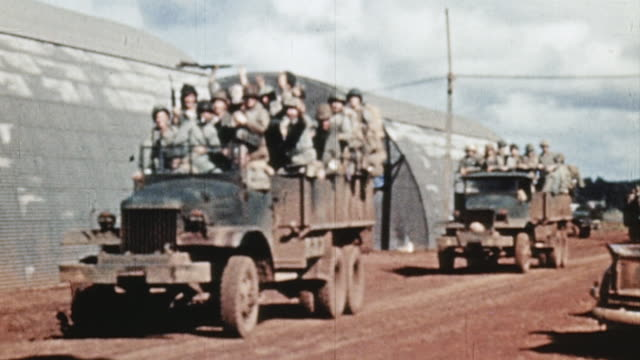 Marines in trucks and Jeeps driving through base past Quonset huts / Pearl Harbor Hawaii United States