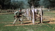 S Marines in warfare training approaching and bayoneting suspended dummies then advancing on in obstacle course during WWII