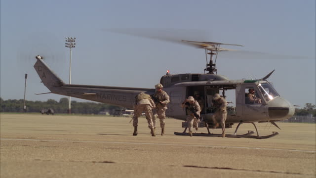 U.S. Marines kneel in a defensive grid after they exit a UH-1 Huey which deploys to another location on an airbase.