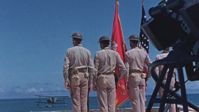 S Marines standing at attention in single line holding American flag and USMC flag facing toward sea