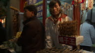 MS Market seller in earmuffs with dried seahorses on stick in foreground, Beijing, China