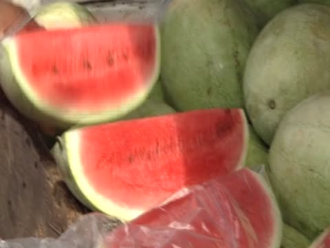Marketeers cut and sell watermelon as market is reopened following police operation to capture notorious drugs baron Christopher ÔDudusÕ Coke lie on...