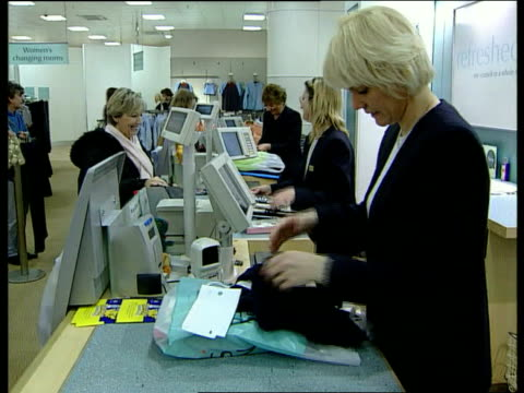 Marks and Spencer profits continue to fall LIB London Marks Spencer Sales assistants behind counter in Marks Spencer clothes department TCMS Clothing...