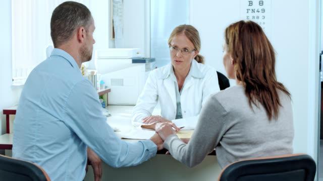 Verheiratet paar Beratung der weiblichen Arzt in Ihrem Büro