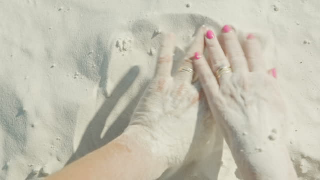 Married couple Hands buried in the sand making love on the beach