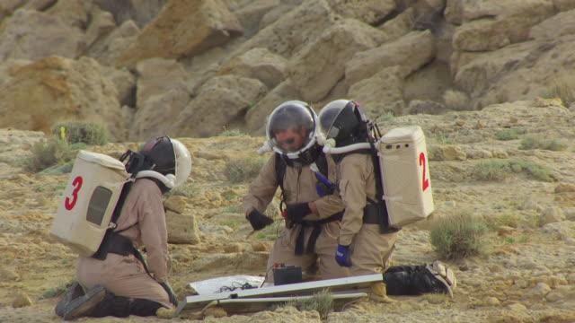 CU AERIAL Mars Desert research station EVA team checking solar device at San Rafael desert / Utah, United States