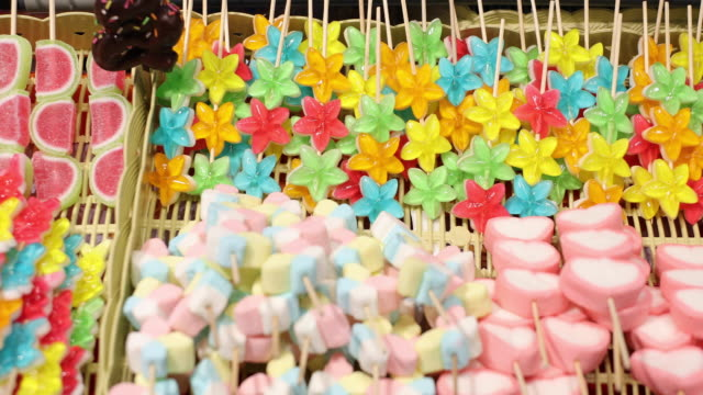 Marshmallows and thai desserts are in the tray.