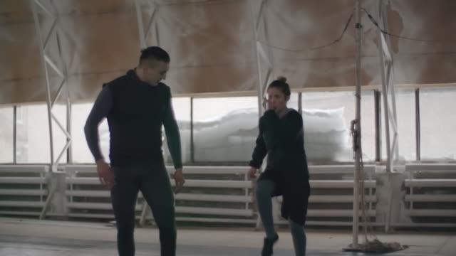 Martial arts coach training a female athlete