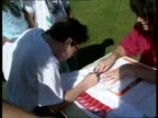 Charity walk ITN ENGLAND Surrey Reigate TCS Martin Conway signing sponsored walk sheet CS Conways hand holding pen singing PULL OUT TCS Conway...