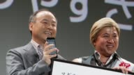 Masayoshi Son president of SoftBank Corp left holds the company's Aquos Phone Xx 206SH smartphone manufactured by Sharp Corp as he stands with...
