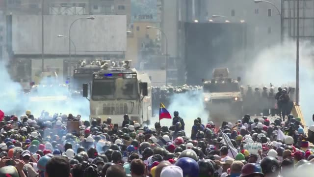 Masked and helmeted Venezuelan protesters take refuge behind wood and metal shields as riot cops fire tear gas and water cannon stopping their...
