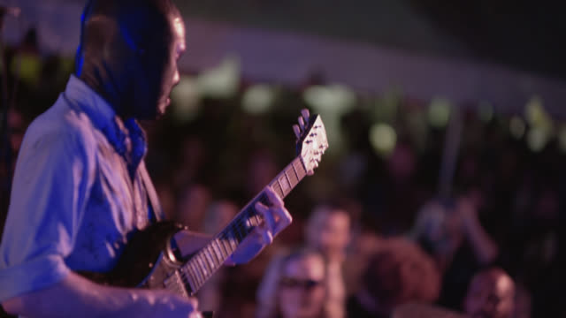 Masked man plays guitar with rock band to enthusiastic crowd at outdoor music festival
