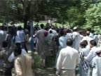 Masked men with guns watch running crowd during the confrontations at the Red Mosque complex July 2007