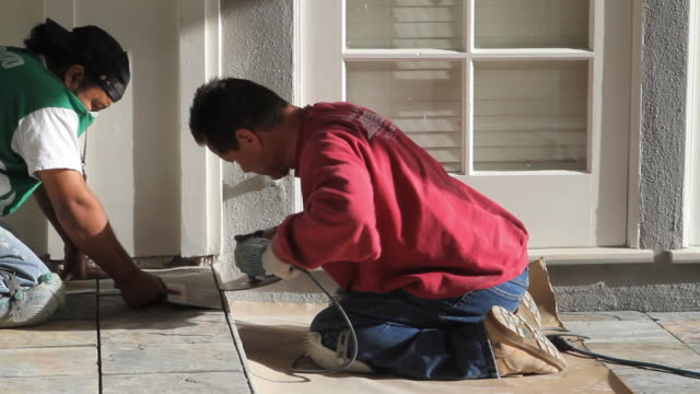 WS Masons adjusting tile into place / North Hollywood, California, USA