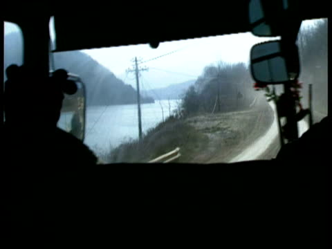 Mass grave uncovered in Kamenica / POV from bus coach en route to village along windy road by lake wreckages of burned houses by roadside / Bosnian...