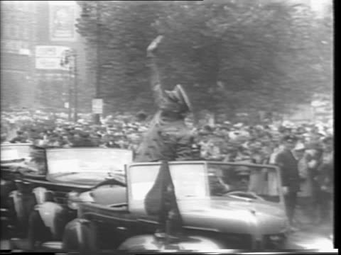 Mass of confetti between buildings as motorcade moves from City Hall uptown / General Dwight Eisenhower waving from car as it proceeds uptown /...