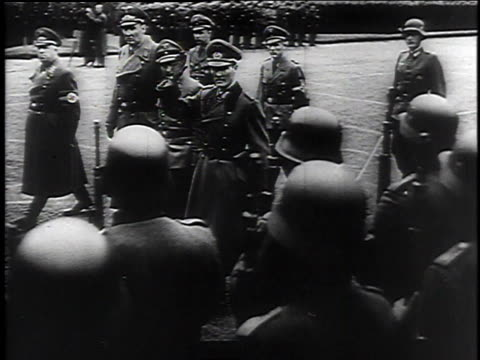Masses of Hitler Youth in formation in a city square / Wehrmacht officers in uniform march past waving / ranks of Hitler Youth with swastika armbands...