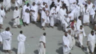 Massive crowds cross pavement in Saudi Arabia.