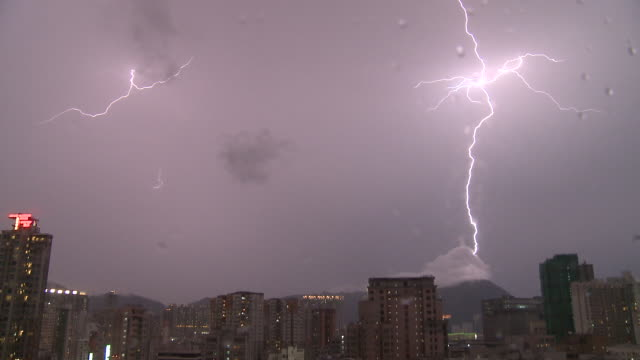 Massive fork of lightning strikes a mountain top at night, Hong Kong