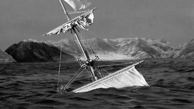 B/W MS mast + top sail of sailing ship sinking in ocean with mountains in background