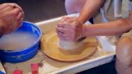 Meester en leerling leren klei knutselen tijdens workshop
