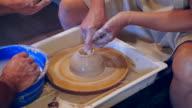 Meester en leerling modellering van klei pot op aardewerk wiel
