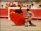 Matador using red cape to taunt charging bloody bull with banderillas in neck / audience in background