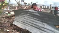 Materials are in short supply for those wanting to rebuild their homes in the typhoon hit city of Tacloban CLEAN Philippines people search for...