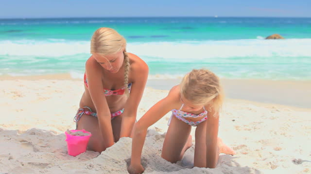 Mather playing with daughter in the sand / Cape Town, Western Cape, South Africa