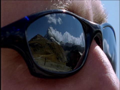 Matterhorn reflected in man's sunglasses then sunglasses removed Switzerland
