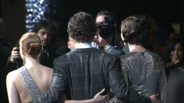 Matthew McConaughey posing for cameras with Anne Hathaway and Jessica Chastain