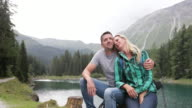 Mature adult couple by lake embracing and enjoying nature