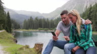 Mature adult couple by lake looking at smart phone
