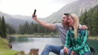 Mature adult couple by lake taking selfie with smart phone