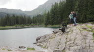 Mature adult couple on rock by lake enjoying scenic nature landscape