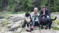 Mature adult couple playing with dogs in forrest