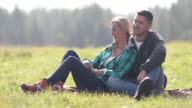 Mature Adult couple sitting in grass enjoying the view