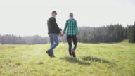 Mature Adult Couple walking and putting out blanket for picnic