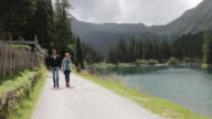 Mature adult couple, walking by scenic nature landscape and lake