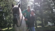 Mature Adult man helping woman from horseback