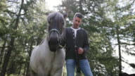 Mature Adult Man holding horse in forrest
