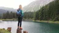 Mature adult woman by lake enjoying scenic nature landscape
