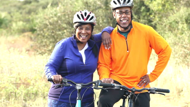 Mature African American couple biking together