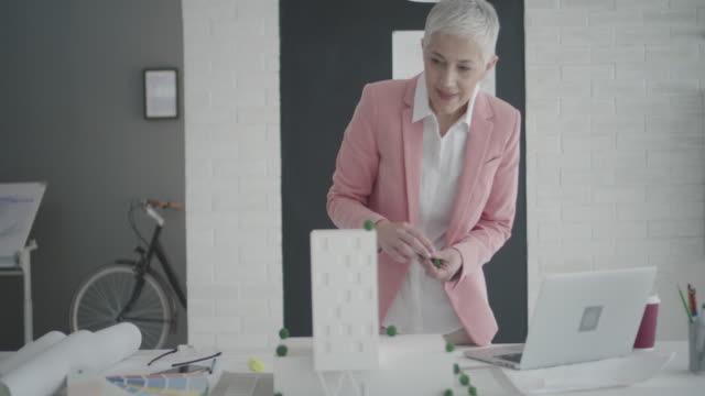 4K: Mature Architect working in her office.