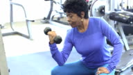 Mature black woman at the gym lifting hand weight