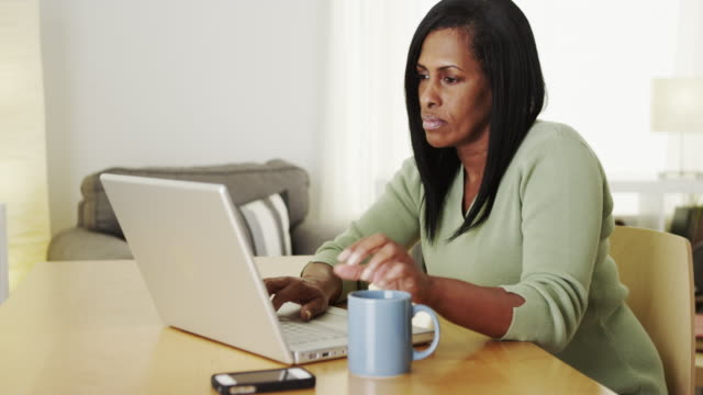 Mature black woman working on laptop computer at desk
