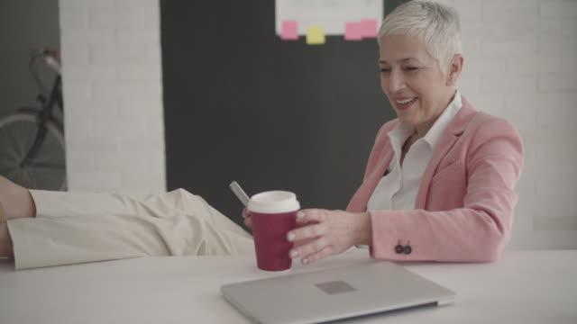 Oudere zakenvrouw met behulp van slimme telefoon In haar kantoor.