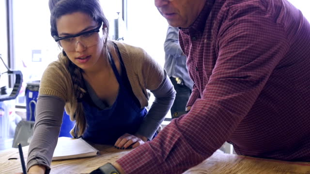 Mature Caucasian male and young Hispanic woman measure plywood in community woodworking shop