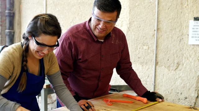 Mature Caucasian man and young Hispanic woman working together in workshop